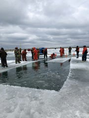 A large hole was cut in the ice so a pickup could be removed from Lexington Harbor Sunday.