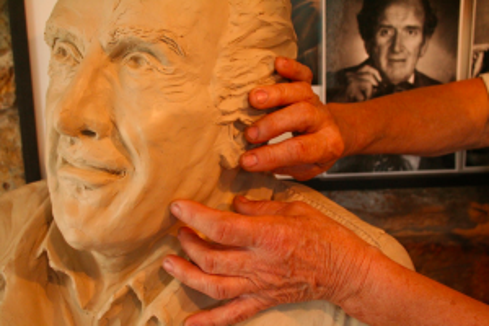 Lorann Jacobs' hands at work on a sculpture of Bill Schintz