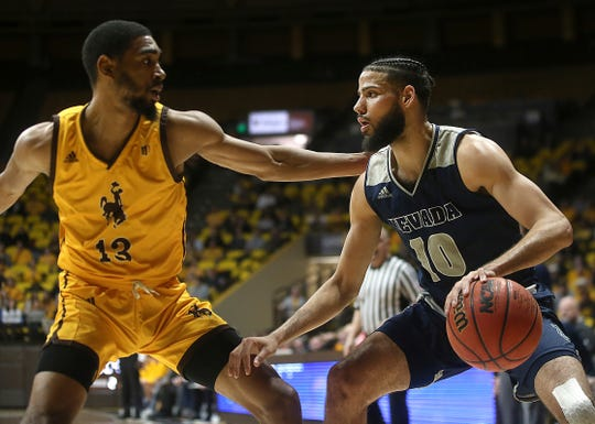 Nevada forward Caleb Martin (10) is defended by Wyoming guard Trevon Taylor (13) during the second half Saturday in Laramie, Wyo.