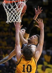 Nevada forward Trey Porter (15) fights to put the ball in the net while being blocked by Wyoming forward Hunter Thompson (10) during the second half Saturday in Laramie, Wyo.