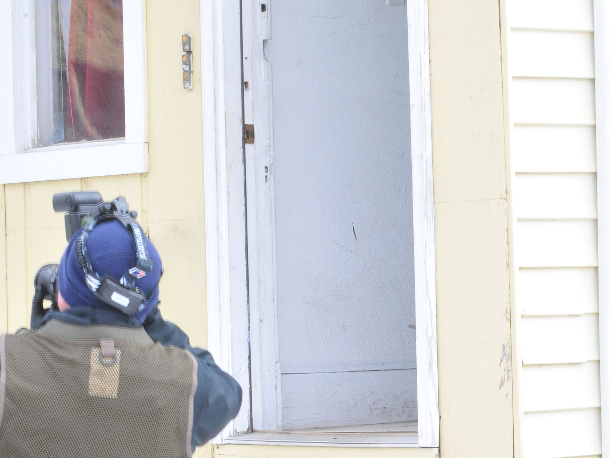 Detective Gerard Longnecker takes photographs outside the door investigators used to access the scene of a shooting Monday in the 2100 block of Grand Boulevard.