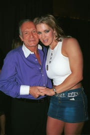 """Playboy founder Hugh Hefner poses with former wrestler, Joanie """"Chyna"""" Laurer, in 2002. Laurer will be inducted into the WWE Hall of Fame in April."""