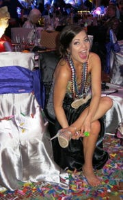 Tiffany Cargill sheds her shoes and gets ready to party at Krewe Ambassadeurs-Minden Grand Bal.