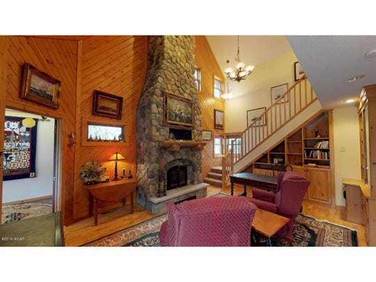 One fireplace soars two stories high to the vaulted ceiling of the wood-paneled family room that branches off from the main entrance.