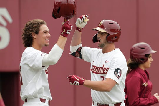 Florida State Seminole outfielder Reese Albert (23) takes a large bite out of a cookie  and fist bumps with Florida State Seminole outfielder Elijah Cabell (19) after Albert hit his first home fun of the season during the seasoner opener against the Maine Black Bears, Friday Feb. 15, 2019.