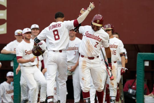 Florida State Seminole outfielder J.C. Flowers (8) fist bumps Florida State Seminole infielder Nander De Sedas (2) after Flowers hit his first home run of the season during the season opener against the Maine Black Bears, Friday Feb. 15, 2019.