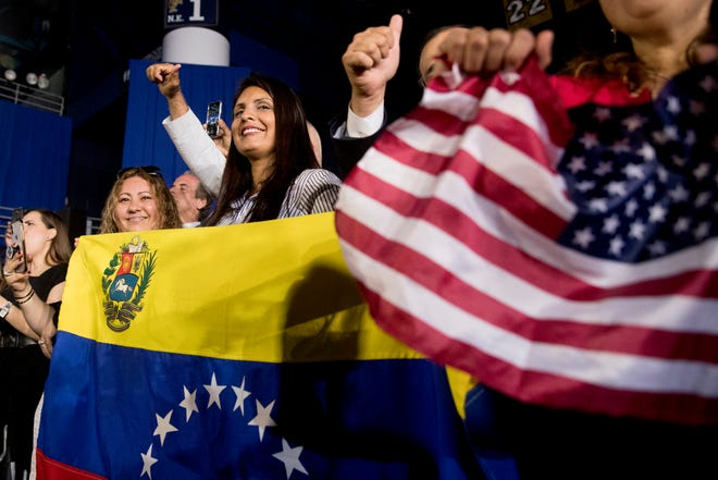 Members of the audience wave Venezuelan and American flags as President Donald Trump speaks to a Venezuelan-American community at Florida Ocean Bank Convocation Center at Florida International University in Miami, Fla., Monday, Feb. 18, 2019, to speak out against President Nicolas Maduro's government and its socialist policies.