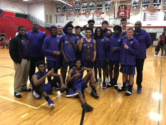 Okeechobee's boys basketball team celebrates after winning the District 13-7A championship on Feb. 16 at South Fork High School.