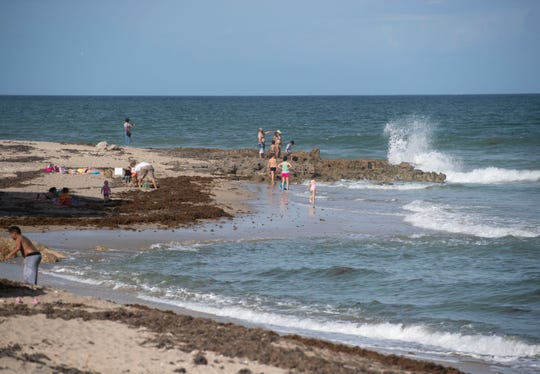 Beachgoers spend a sunny day at Bathtub Reef Beach on Friday, Feb. 15, 2018, on Hutchinson Island in Martin County. Many sunscreens contain the common, coral-damaging chemicals oxybenzone and octinoxate. The largest coral reef in North America, the Florida Reef Tract, stretches 360 miles between the St. Lucie Inlet and the tip of the Florida Keys.