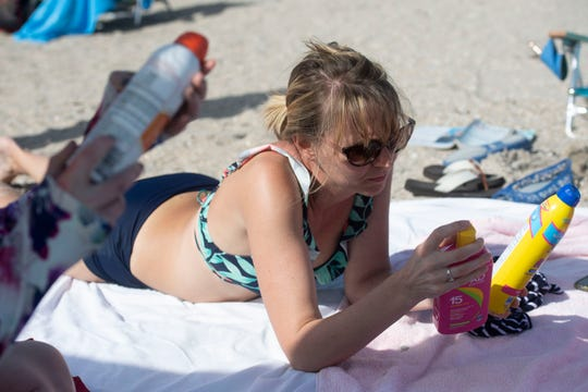Kelly Pelc, of Arendtsville, Pa., examines her sunscreen on a sunny day at Bathtub Reef Beach on Friday, Feb. 15, 2018, on Hutchinson Island in Martin County. Many sunscreens contain the common, coral-damaging chemicals oxybenzone and octinoxate. The largest coral reef in North America, the Florida Reef Tract, stretches 360 miles between the St. Lucie Inlet and the tip of the Florida Keys.