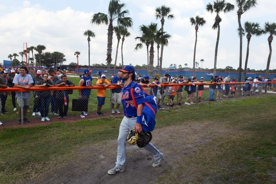 New York Mets fans line the fence as catcher Colton Plaia walks between fields on Monday, Feb. 18, 2019, during a full-squad workout at First Data Field in Port St. Lucie. The Mets will play the Atlanta Braves on Feb. 23 for the first spring training game of the season.