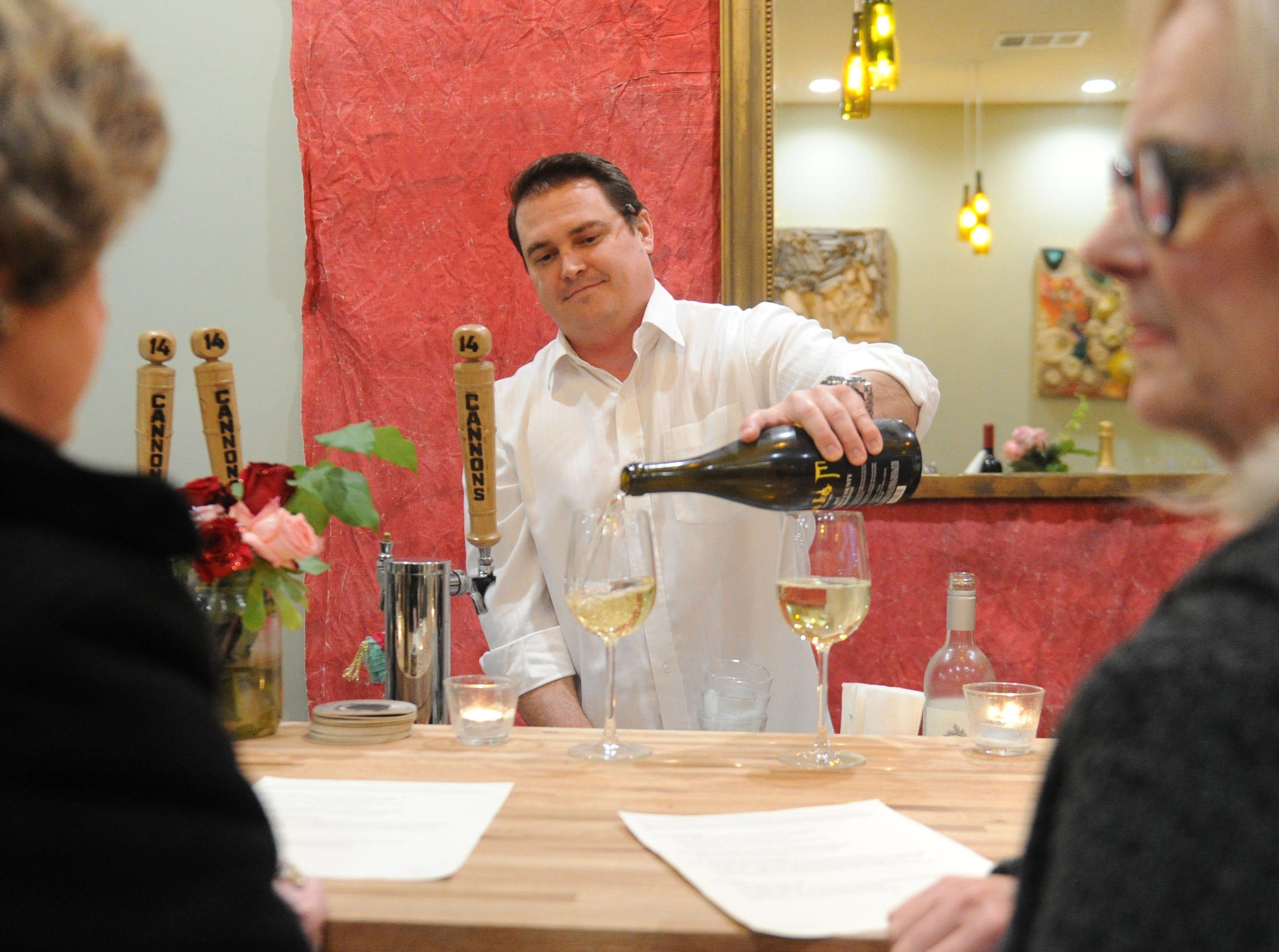 Graham Harris, owner of Decker Kitchen in Westlake Village, pours wine for guests Carole Gordon, left, and her friend Susan Bevan.