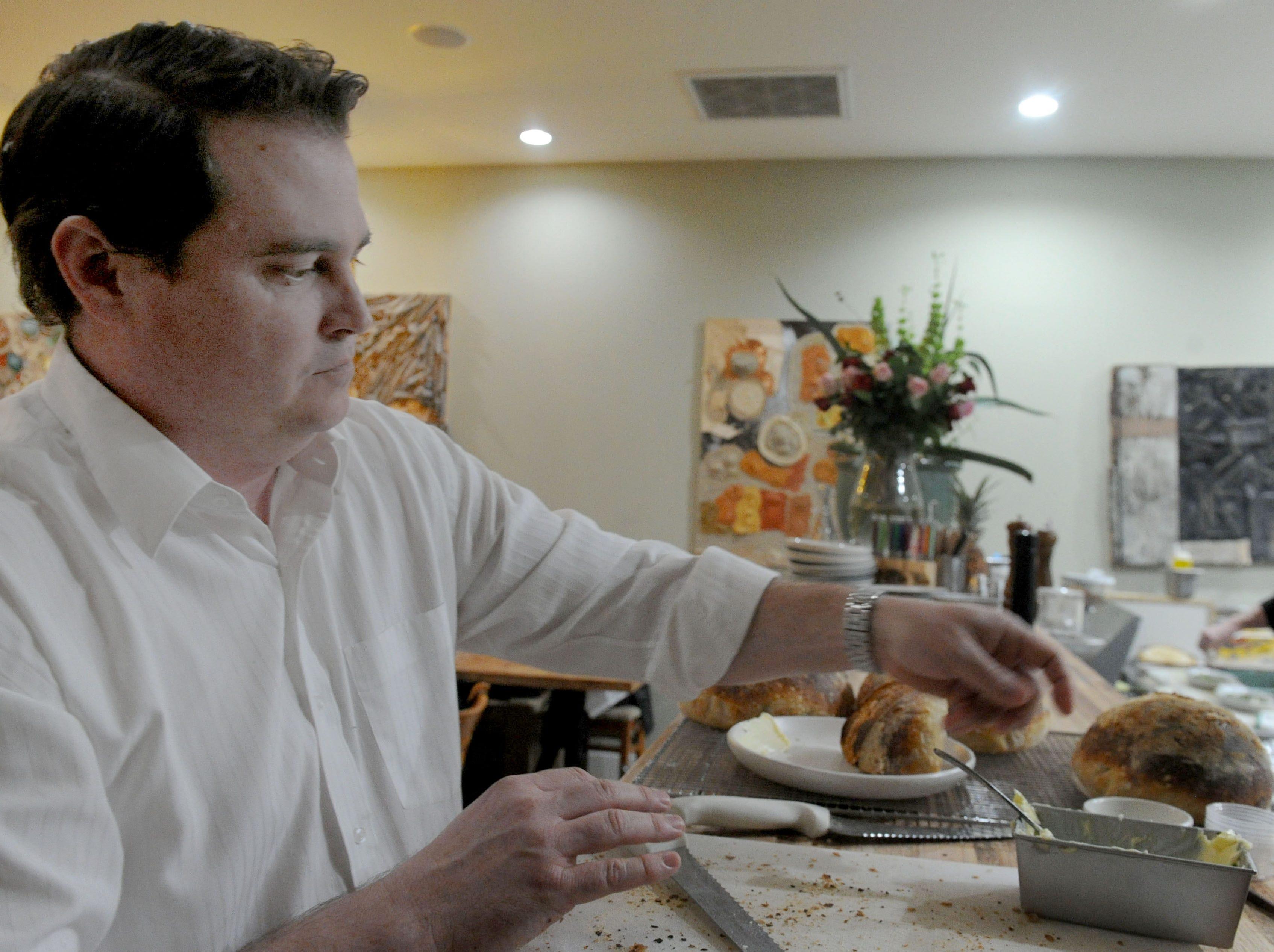 Graham Harris, owner of Decker Kitchen in Westlake Village, cuts homemade bread for customers.