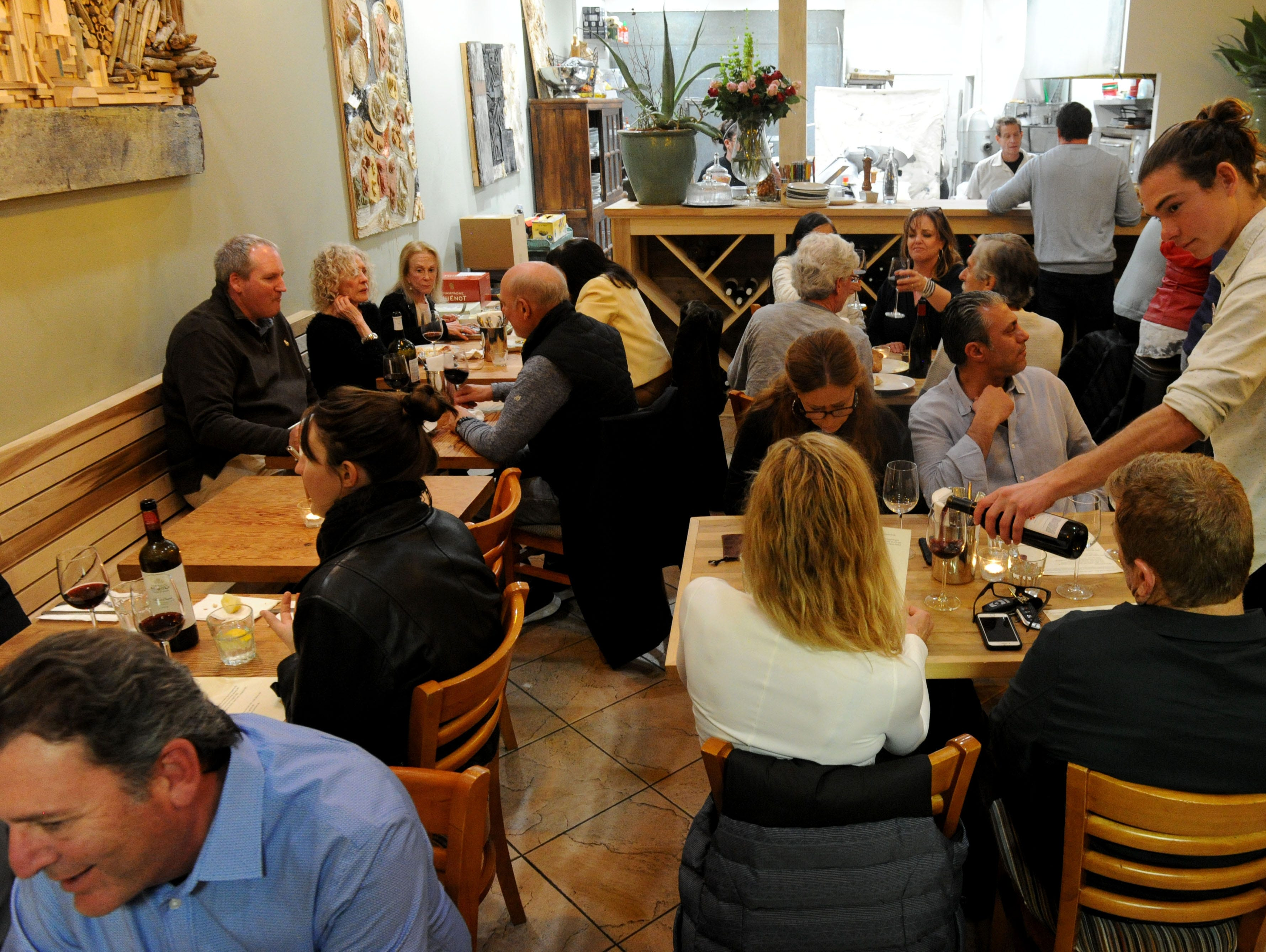 Alex Mitchell, waiter at Decker Kitchen in Westlake Village, pours wine for customers.