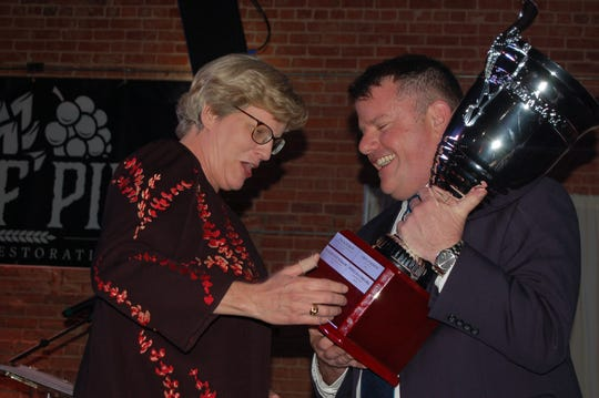 Phyllis Cowling, president and CEO of United Regional Health Care System, reacts to the hospital being recognized as Member of the Year at the 2019 Wichita Falls Chamber of Commerce annual meeting. Chamber President Henry Florsheim, right, hands Cowling the trophy.