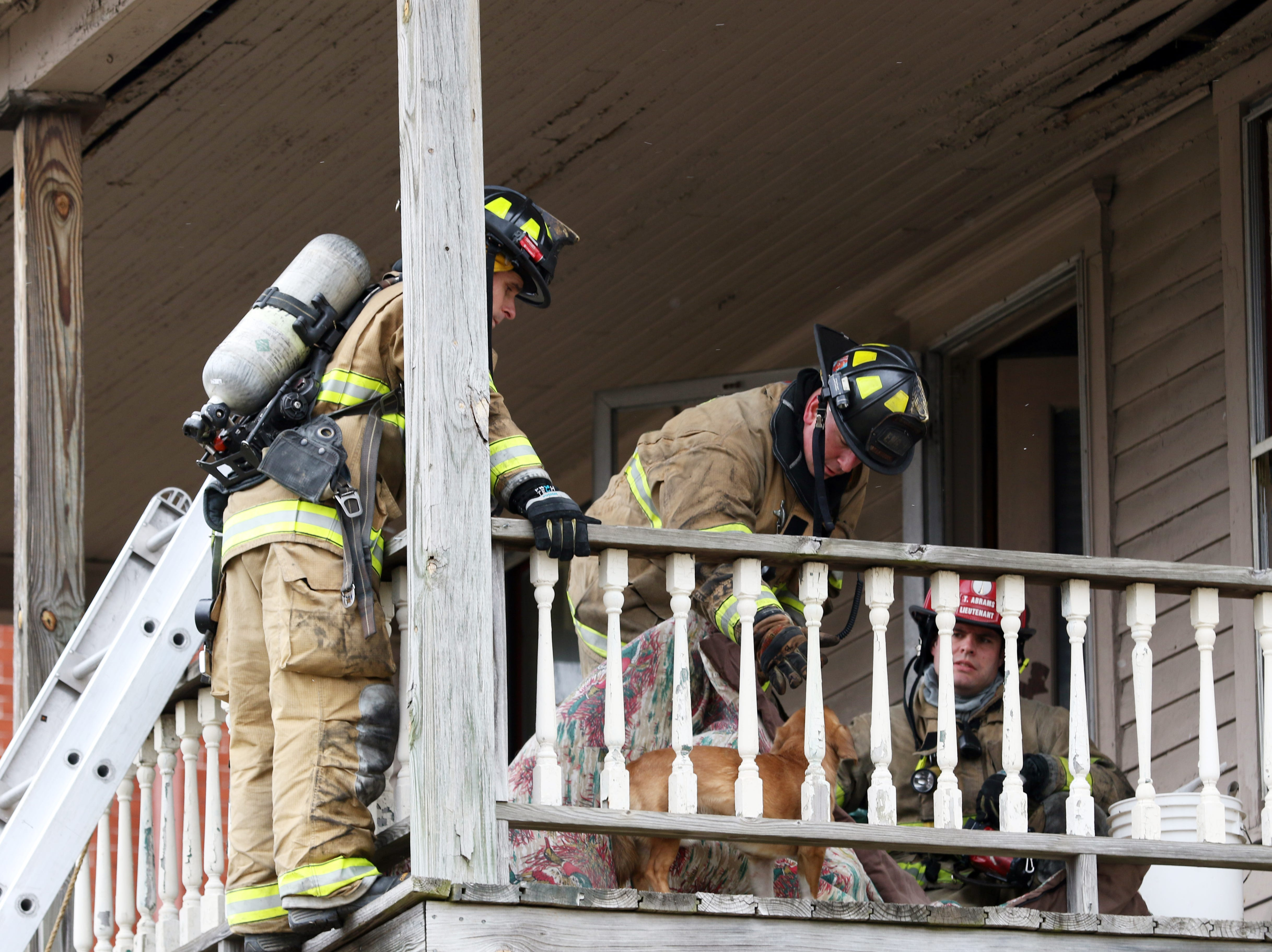 The Zanesville Fire Department fought a fire at 924 Maple Avenue in Zanesville Monday afternoon. Two people were taken to the hospital because of the blaze. Firefighters try to coax a dog from the porch after the fire. The dog was unenthusiastic about the rescue, but was safely removed from the porch.