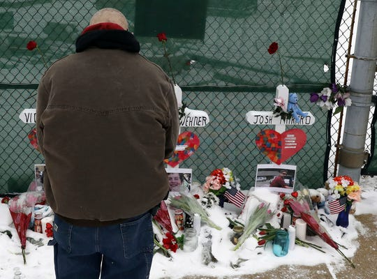 A man prays at a makeshift memorial Feb. 17 in Aurora, Ill., near the Henry Pratt manufacturing company where five people were killed Friday.