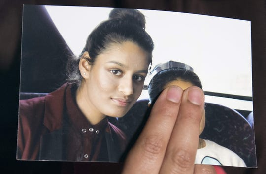 A family member of Shamima Begum holds a picture of the British girl, left, while being interviewed by the media in London on Feb. 22, 2015.