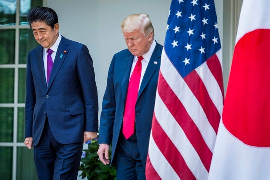 President Donald Trump and Japanese Prime Minister Shinzo Abe walk from the Oval Office to the Rose Garden for a joint news conference at the White House on June 7, 2018.
