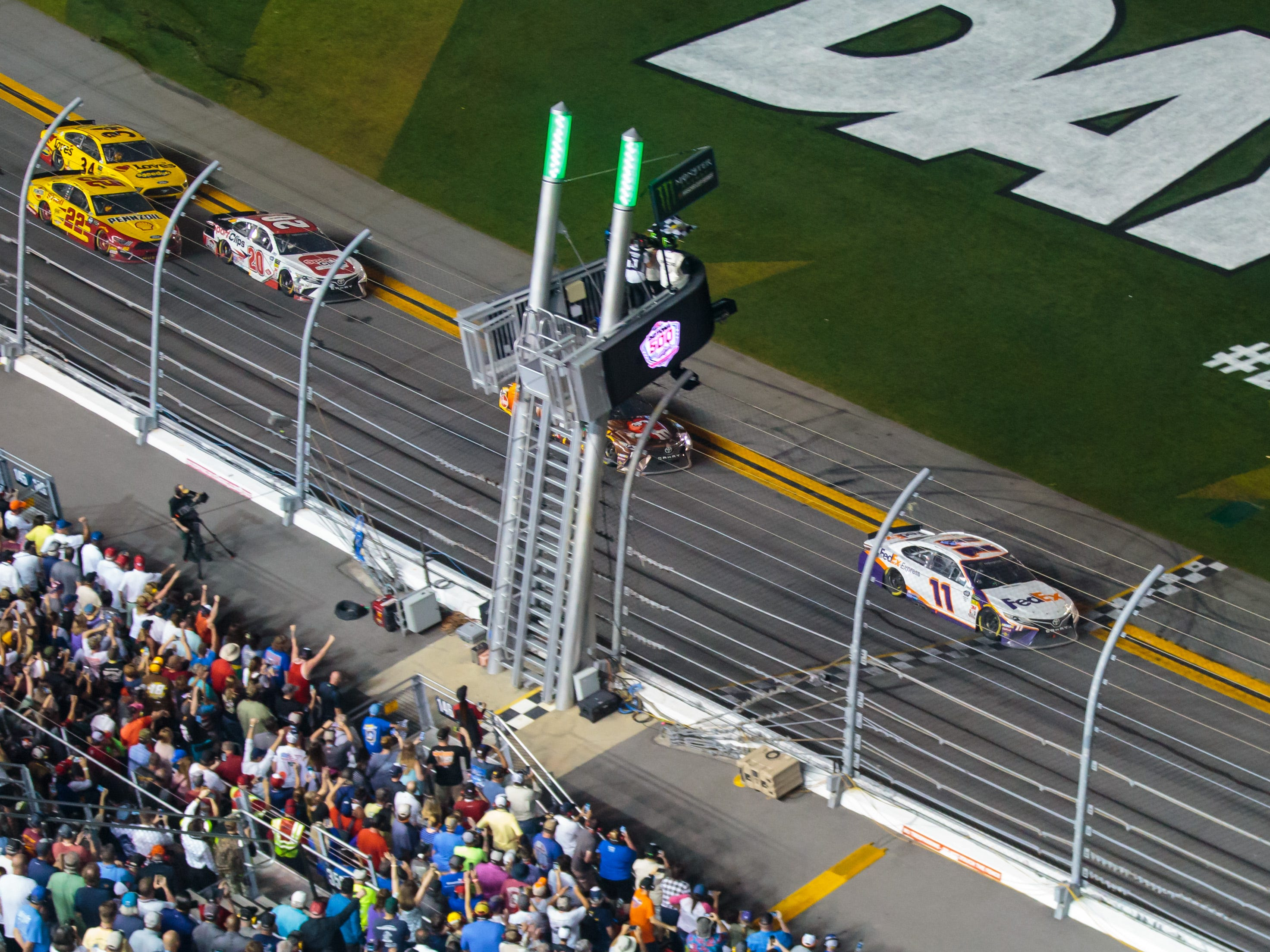 NASCAR Cup Series driver Denny Hamlin (11) takes the checkered flag to win the Daytona 500 at Daytona International Speedway.