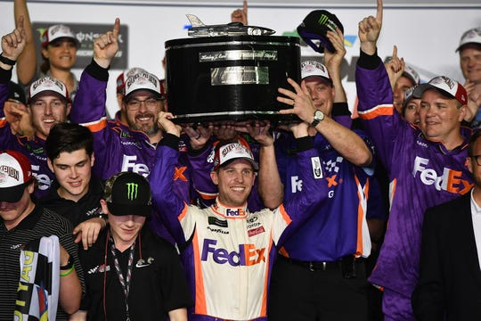 Denny Hamlin celebrates with the Harley J. Earl Trophy after winning the 61st Daytona 500.