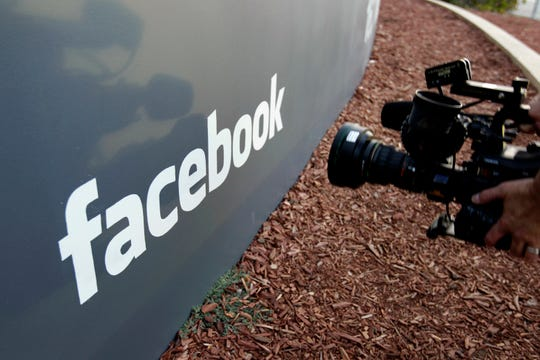 In this May 18, 2012, file photo, a television photographer shoots the sign outside of Facebook headquarters in Menlo Park, Calif.