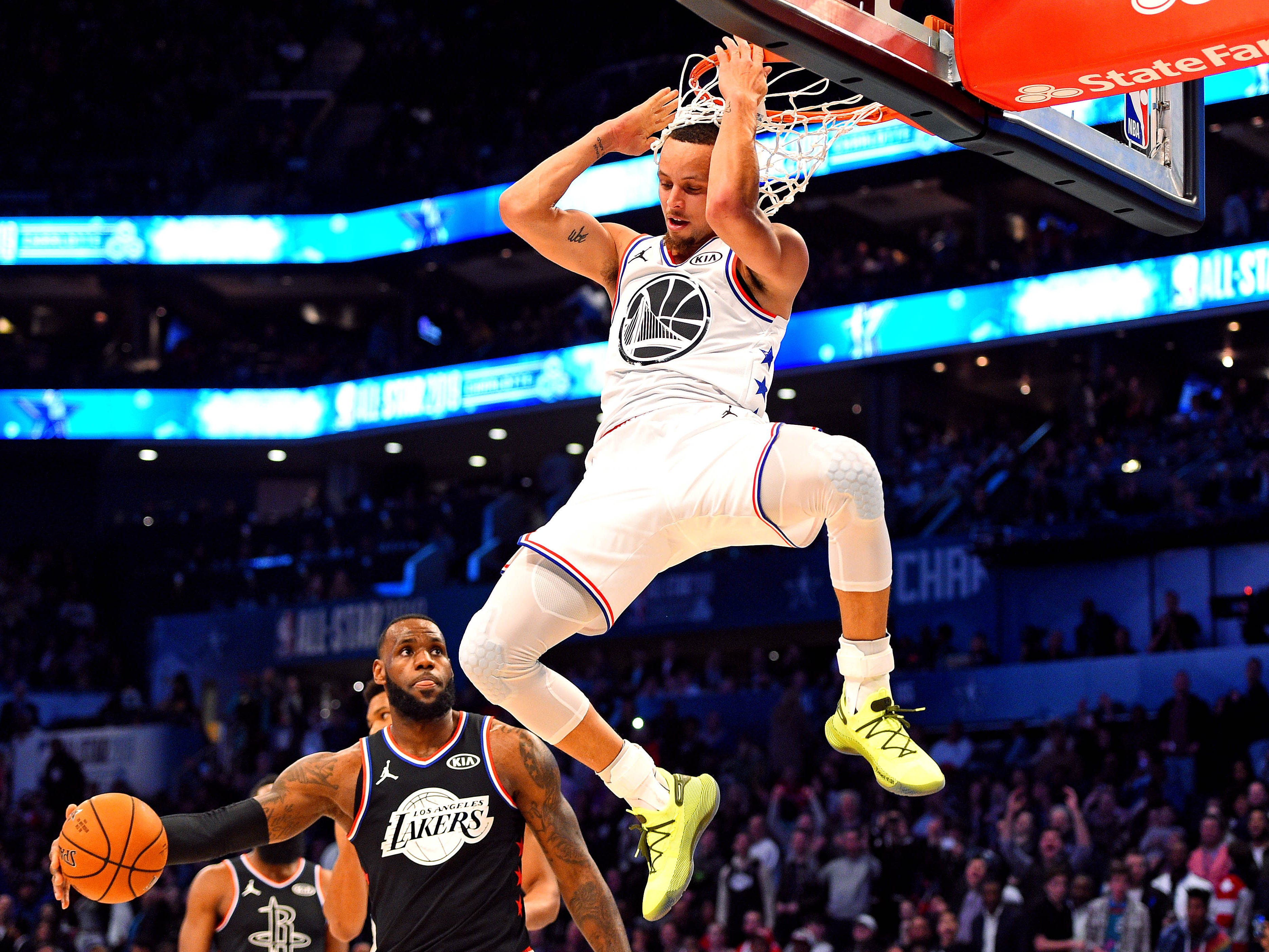Steph Curry hangs on the rim after throwing down a dunk in the All-Star Game.