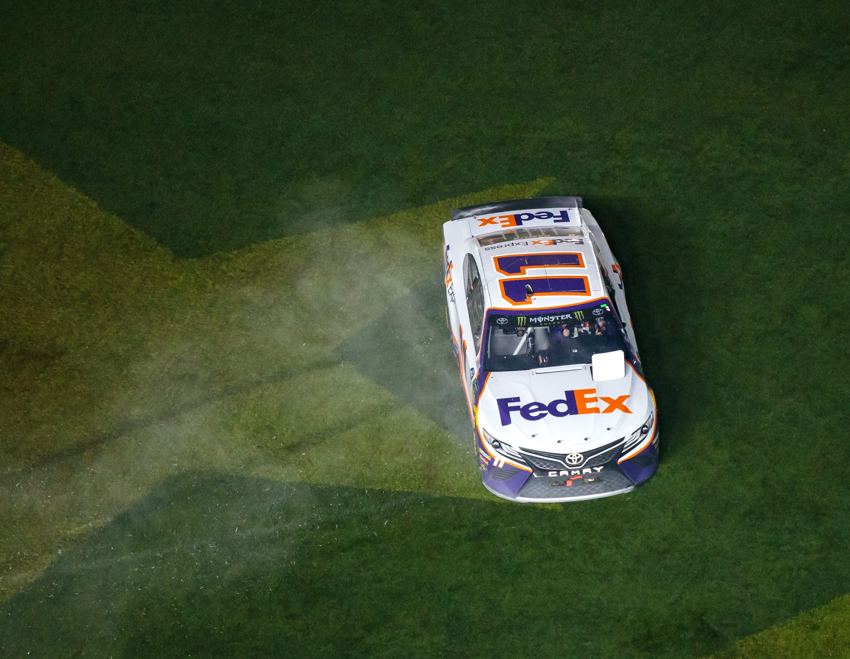Denny Hamlin does a burnout onto the infield grass at Daytona International Speedway after winning the 2019 Daytona 500.