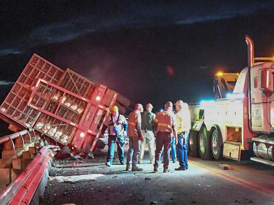 Anderson County firemen, ambulance, and troopers at the scene of a tractor-trailer with cages of chickens and a sedan on a bridge over Lake Hartwell on state highway 24 in Anderson Monday evening. One person died after the Ford Taurus collided with an tractor-trailer.
