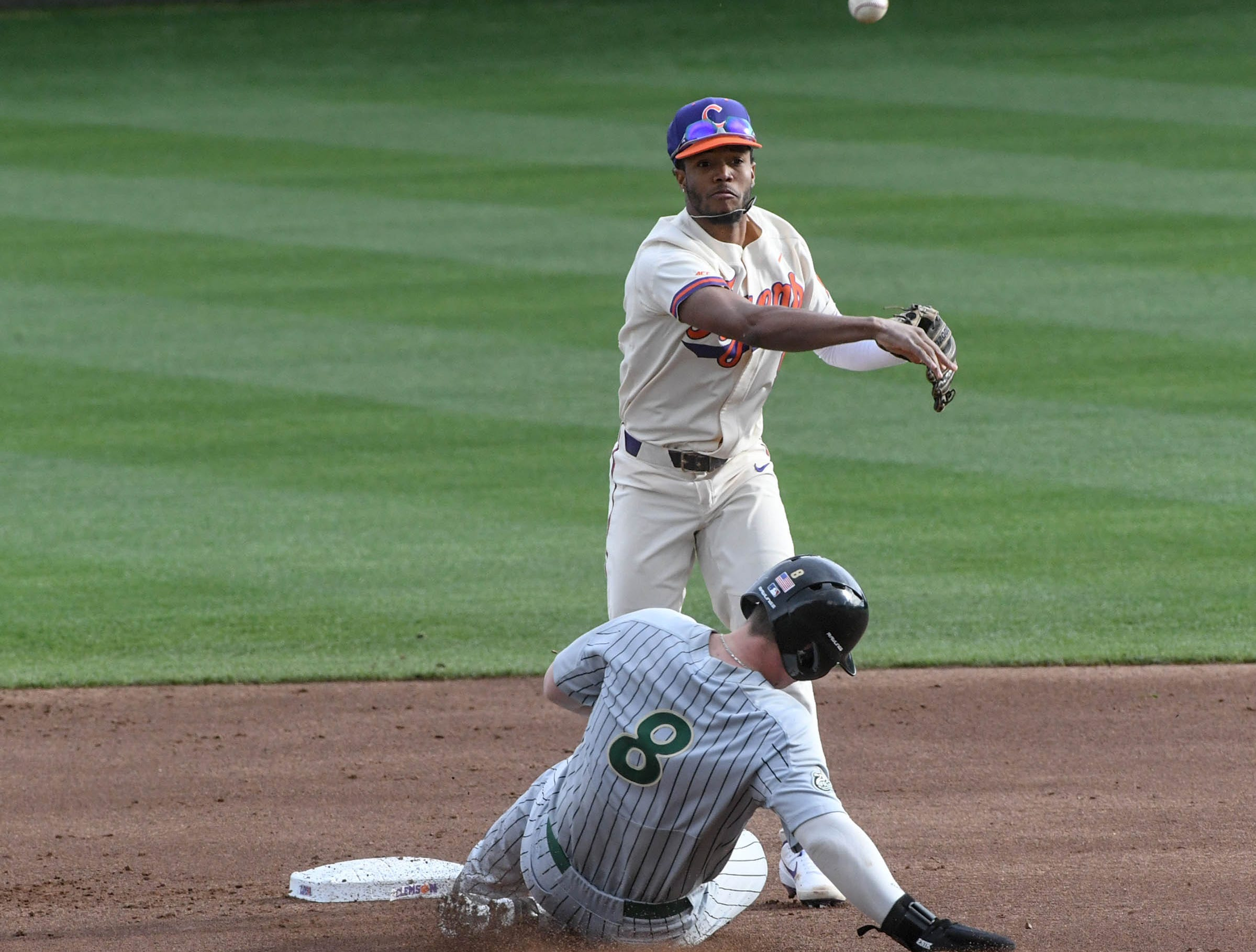 Clemson infielder Jordan Greene(9) turns a double play near Charlotte senior Harris Yett(8) during the top of the first inning at Doug Kingsmore Stadium in Clemson Monday, February 18, 2019.