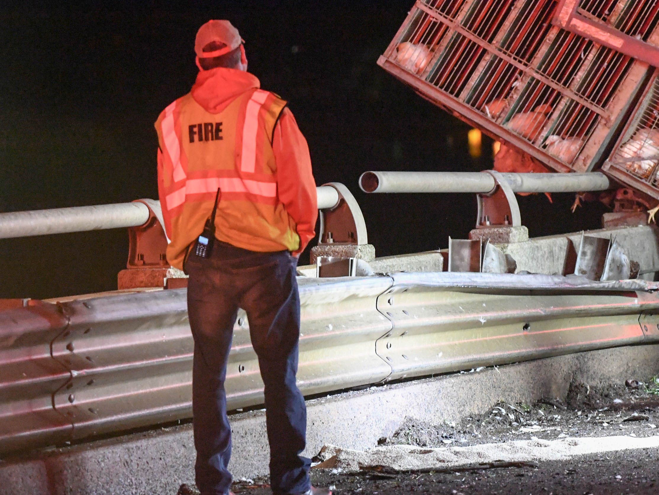 A fireman looks at cages with live chickens leaning on a broken guard rail on a bridge over Lake Hartwell on state highway 24 in Anderson Monday evening. One person died after the Ford Taurus collided with an tractor-trailer.