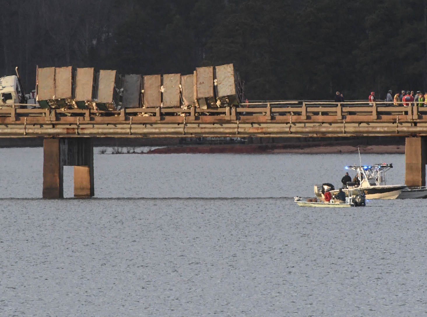 Emergency workers look at damage from an accident with a tractor-trailer with cages of chickens and a sedan on a bridge over Lake Hartwell on state highway 24 in Anderson Monday evening. One person died after the Ford Taurus collided with an tractor-trailer.
