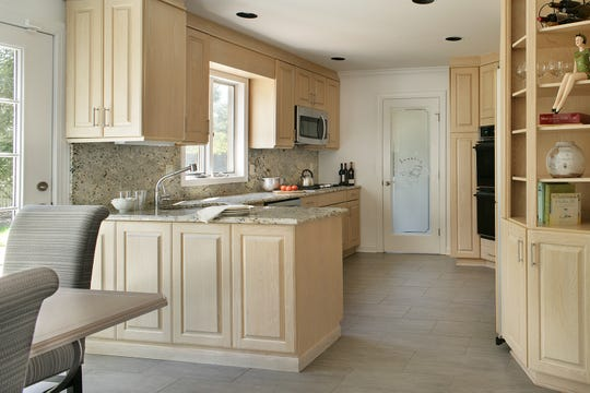 """In the kitchen, the original pink laminate countertops and dining table were swapped for granite countertops and backsplash. The cabinetry is the same but updated with simple polished and brushed chrome hardware. The chipped ceramic tile floor was substituted with a gray porcelain tile set in a random brick pattern. A novelty door that reads """"laundry"""" was installed at the end of the kitchen to allow warmth and natural light through, giving the room a spark of personality."""