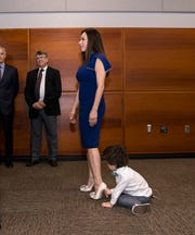 Catherine Tobin Hilliard listens as Nueces County Judge Barbara Canales speaks while her son Dell Hilliard, 3, plays with her heels after being sworn in as Corpus Christi Port Commissioner, six of her seven children were there to see her sworn in, the other was away at college, on February 19, 2019, she will fill out the remainder of of Nueces County Judge Barbara Canales' term on the port commission, which ends Dec. 31, 2019.