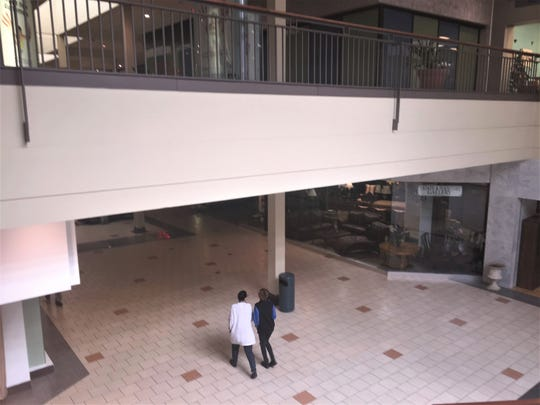 Shoppers walk through a largely deserted mall at Voorhees Town Center.