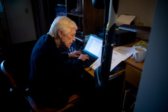 Sr. Rose Ann Fleming writes a brief while watching Xavier play Providence Friars men's basketball team Saturday, February 16, 2019 in her apartment on Xavier University's campus.
