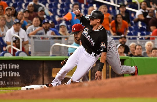 Sep 21, 2018; Miami, FL, USA; Miami Marlins left fielder Derek Dietrich (32) is tagged out by Cincinnati Reds third baseman Eugenio Suarez (7) in the second inning at Marlins Park. Mandatory Credit: Jasen Vinlove-USA TODAY Sports