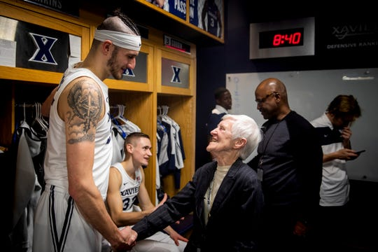 Sr. Rose Ann Fleming congratulates Xavier forward Zach Hankins after his team's victory over Georgetown Wednesday, January 9, 2019 in the locker room at the Cintas Center. Fleming attends every home game and sometimes travels with the team. She went to Hawaii in November for the Maui Jim Maui Invitational.
