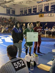 St. Joseph Derek Zelesnick poses after winning the District 14 wrestling title at 138 pounds.
