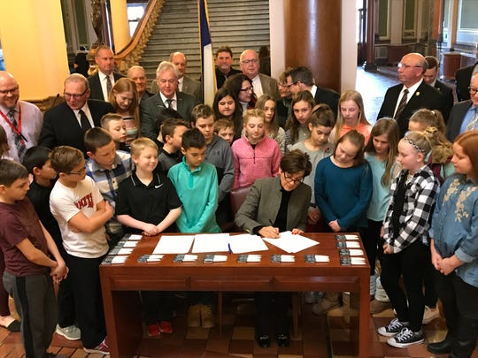 Gov. Kim Reynolds signs legislation funding Iowa's K-12 school system, surrounded by students from North Polk Community Schools and legislative leaders.