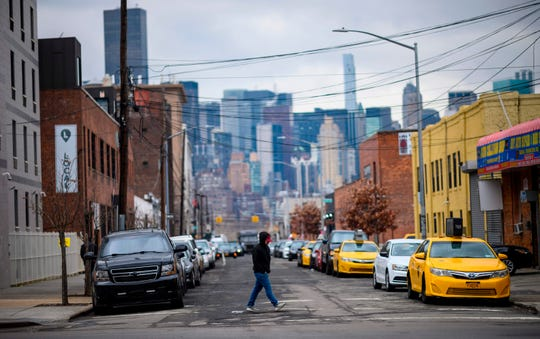 A man walks in a street in Long Island City on Feb. 18, 2019, in the Queens borough of New York City. Seattle-based online retailer Amazon said they are cancelling plans to build a second corporate headquarter in Long Island City after encountering opposition from some local politicians and residents.
