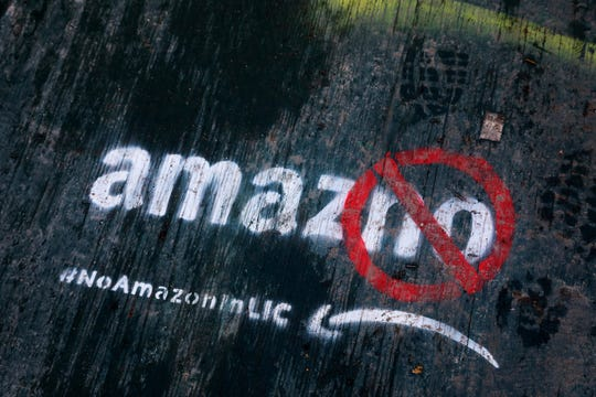 Graffiti has been painted on a sidewalk by someone opposed to the location of an Amazon headquarters in the Long Island City neighborhood in the Queens borough of New York. Amazon said Thursday, Feb. 14, 2019, that it will not be building a new headquarters in New York, a stunning reversal after a yearlong search.