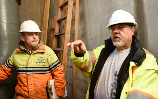 John Ladensack, left, supervisor of MDOT's Auburn Hills garage listens to Dennis Adams, MDOT maintenance mechanic for the Auburn Hills garage, as he talks about how the pumps operate.