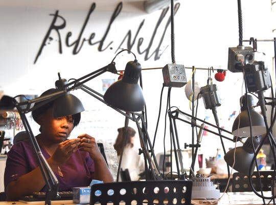 Rebel Nell employee Alicia Preyer of Detroit quality-checks jewelry she recently made in the Rebel Nell studio inside the Ponyride building in Corktown. Rebel Nell jewelry is made from graffiti that has fallen off Detroit buildings.