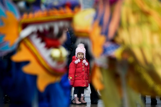 A child watches dragon dance performance during the Lantern Festival organized by city government at a square in Yufa town of Beijing's Daxing district, Tuesday, Feb. 19, 2019. Tuesday is the Lantern Festival in China, the final day of the annual celebration of the Chinese Lunar New Year.