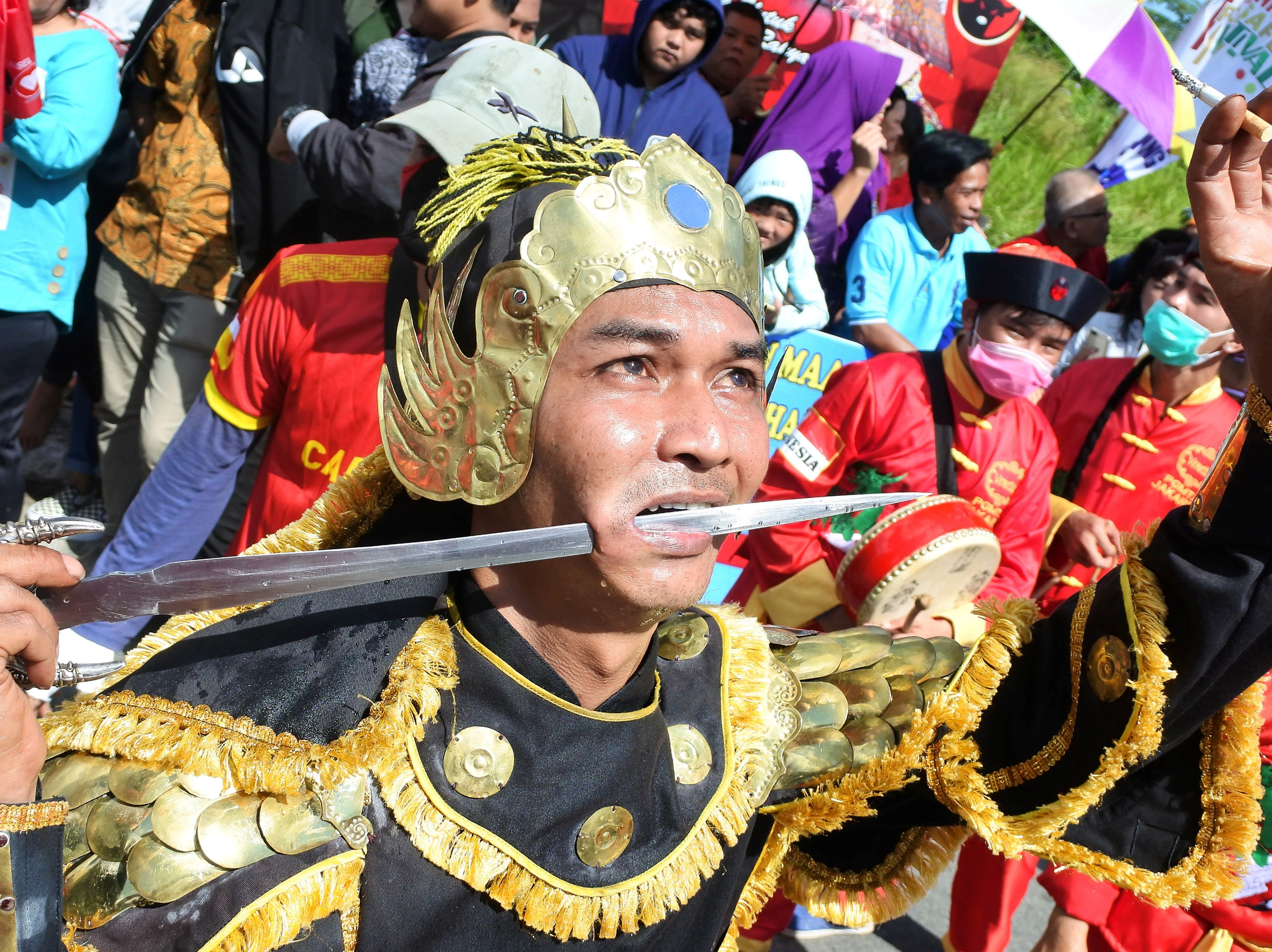 An Indonesian man participates in a parade with a metal sword piercing through his cheek during the Cap Go Meh Festival in Singkawang, West Kalimantan on February 19, 2019. - Chinese Indonesians celebrated the Cap Go Meh festival to mark the end of Lunar New Year festival.