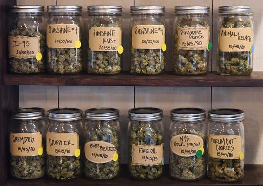 Various marijuana strains with prices line shelves along the walls of the Green House of Walled Lake marijuana dispensary.