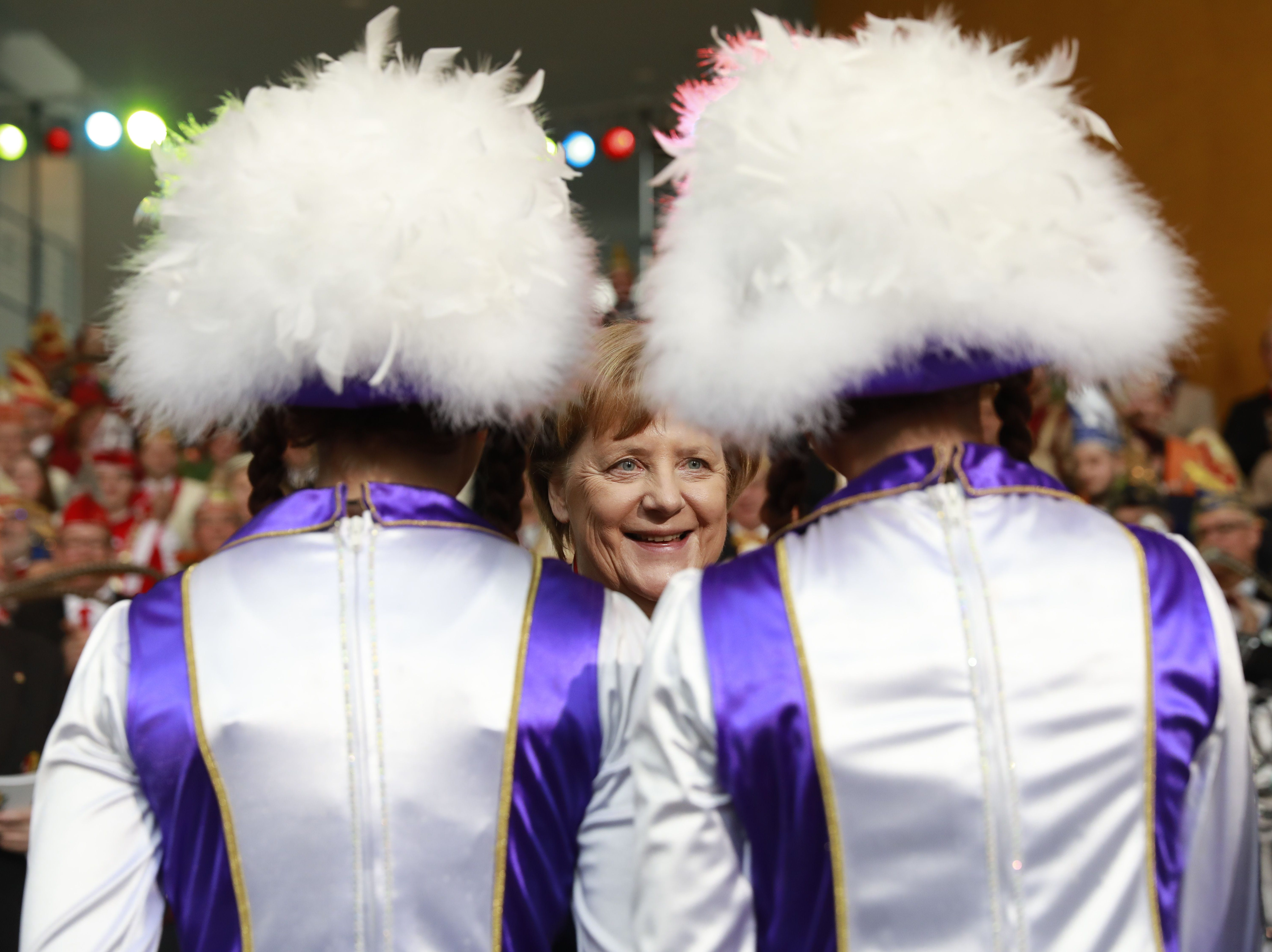 """German Chacellor Angela Merkel talks to a carnival group, during a carnival reception at the chancellery in Berlin on February 19, 2019. - German Chancellor Angela Merkel receives carnivalists and """"Prinzenpaare"""" (carnival pairs)  from different federal states and receives a carnival medal."""