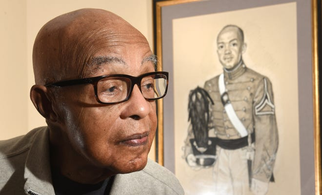Clifford Worthy stands next to a drawing  taken from a 1953 photograph, when he was a West Point cadet.