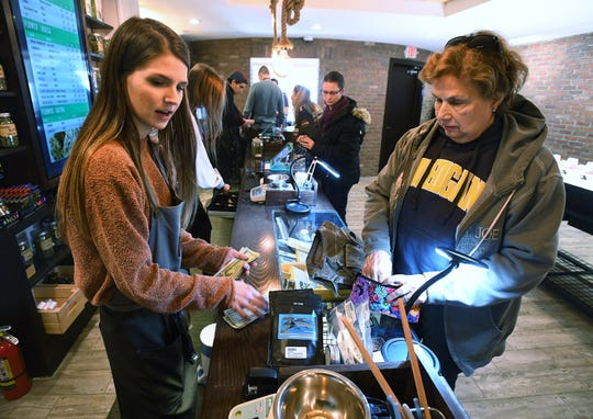 """Cannabis consultant Allana Conn of Green House of Walled Lake, left, assists Meredith DeLong of Clarkston with her purchases of various products for pain management, """"I have a really bad, bad back that I have been taking narcotics for, for years,"""" she said.  """"Marijuana took care of all the pain."""""""